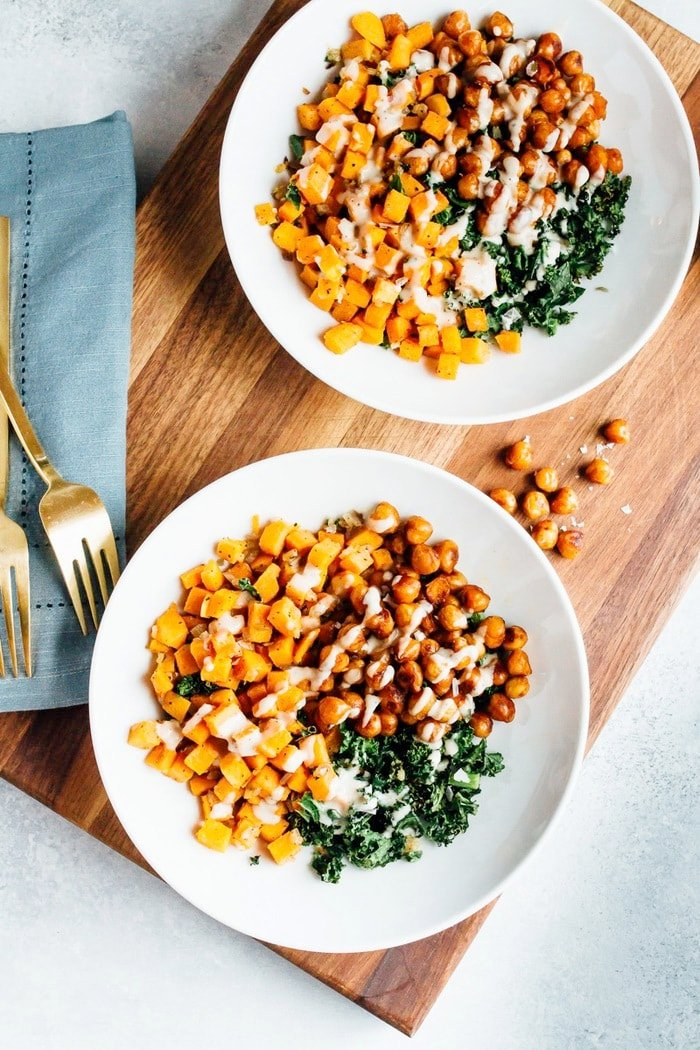 This vegan power bowl is loaded with roasted sweet potatoes and kale, spicy chickpeas and a creamy white bean dressing.