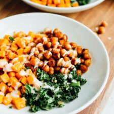 Sweet potato, chick peas and kale on two white plates, sitting on a wooden cutting board.