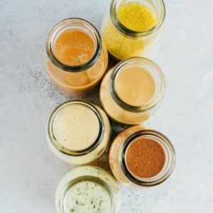 Six glass containers of salad dressings.