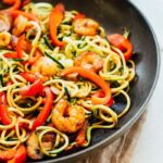 Zucchini noodles, mushrooms, shrimp, red pepper lo mein in a pan.