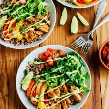 Three plates of chicken fajita quinoa bowls, with chicken, tomato, lettuce, peppers, and jalapeno with 2 forks.