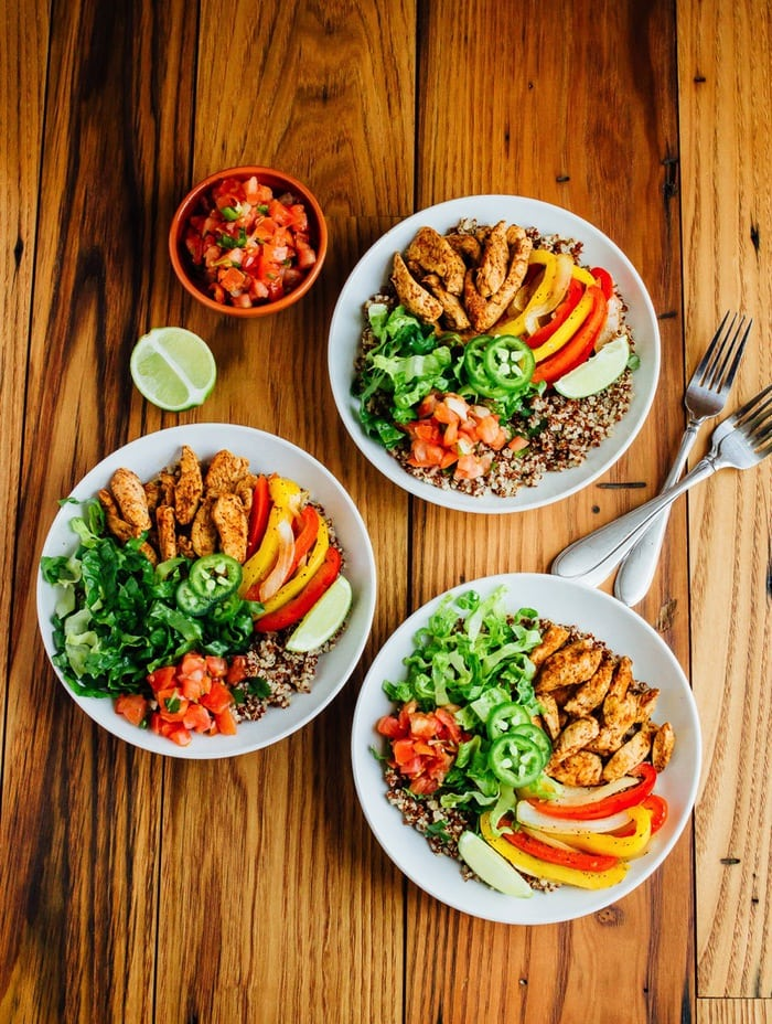 HEALTHY chicken fajita quinoa bowls featuring spiced-up chicken, sautéed peppers and a creamy avocado goat cheese sauce.