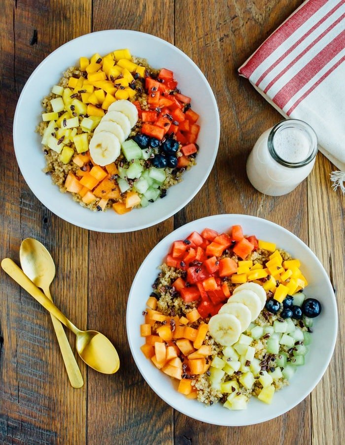 Overhead shot of Cinnamon Quinoa Breakfast Bowls with chopped fresh fruit, served in white bowls on wood table.