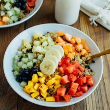 Overhead shot of Cinnamon Quinoa Breakfast Bowls with chopped fresh fruit, served in white bowls on wood table and glass of milk.