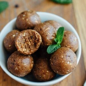 A bowl of thin mint protein balls with a bite taken out of one and fresh mint leaves.