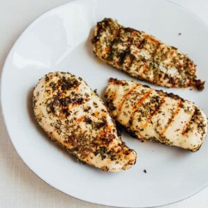 Grilled apple cider vinegar chicken breasts on a white plate.