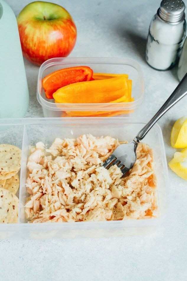 A to-go container full of tuna with a fork in it, sliced peppers in a container in the background.