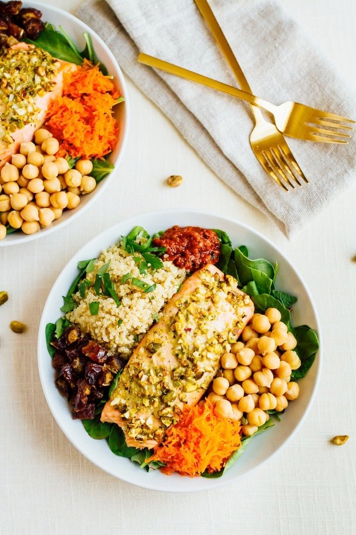 This pistachio salmon salad features pistachio crusted salmon served over a bed of baby spinach with quinoa, chickpeas, carrots, dates and a spicy harissa dressing. It's a delicious meal-sized salad that will fill you up without weighing you down.