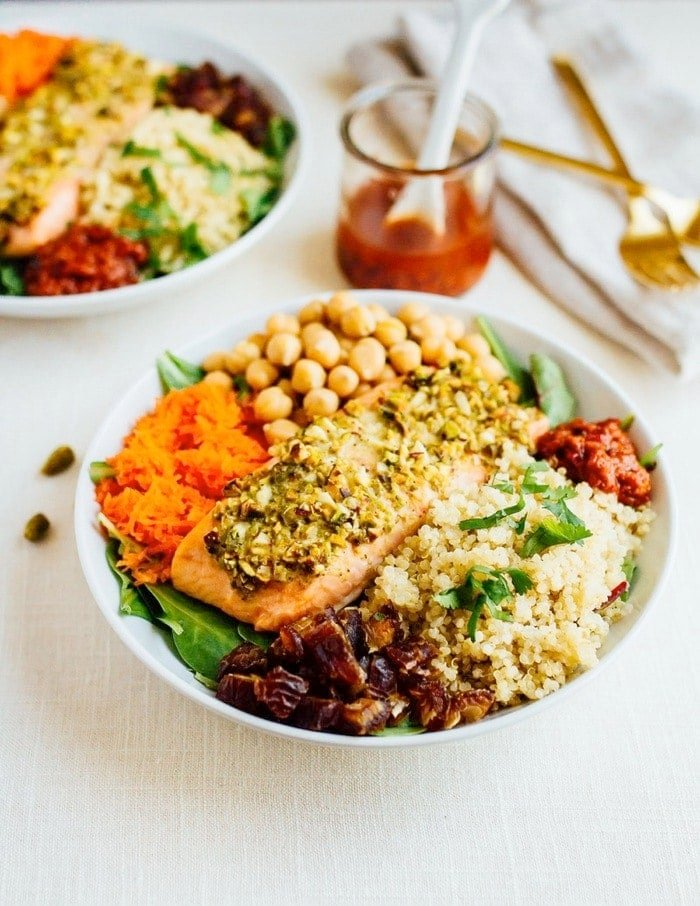 Pistachio Crusted Salmon served over a bed of baby spinach with quinoa, chickpeas, carrots, dates and a spicy harissa dressing with jar of dressing and gold forks in the background.