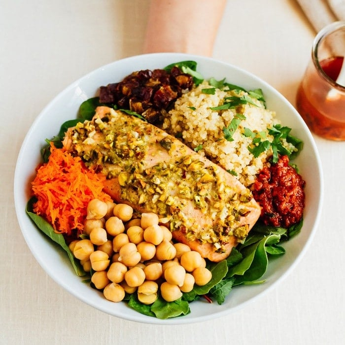 This delicious pistachio salmon salad has a Mediterranean feel with quinoa, chickpeas, carrots, dates and a spicy harissa dressing.