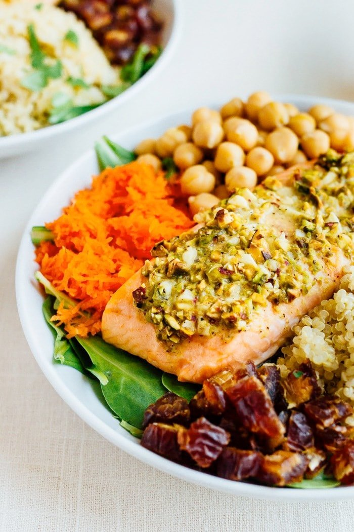 Close-up shot of Pistachio Crusted Salmon served over a bed of baby spinach with quinoa, chickpeas, carrots, dates and a spicy harissa dressing.