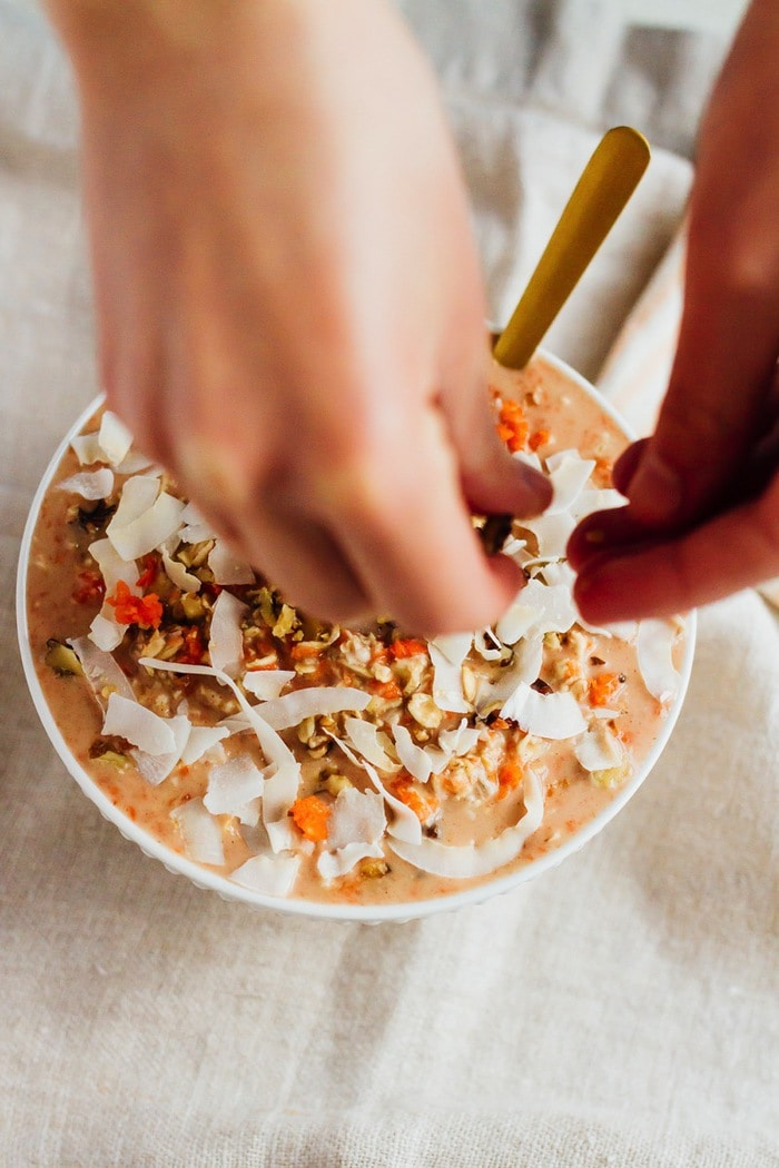 Hands sprinkling coconut on a bowl of carrot cake overnight oats topped with walnuts.