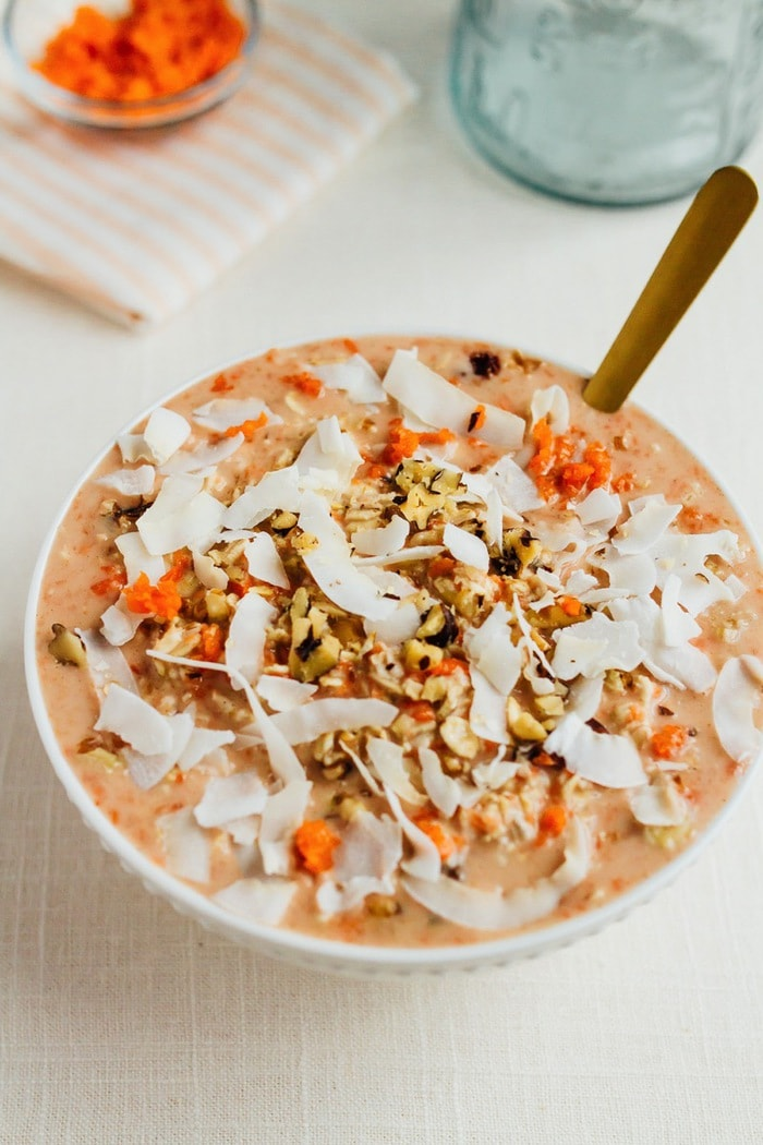 Bowl of carrot cake overnight oats topped with walnuts and coconut.