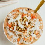 Carrot cake overnight oats with nuts and shredded coconut in a bowl with a spoon.