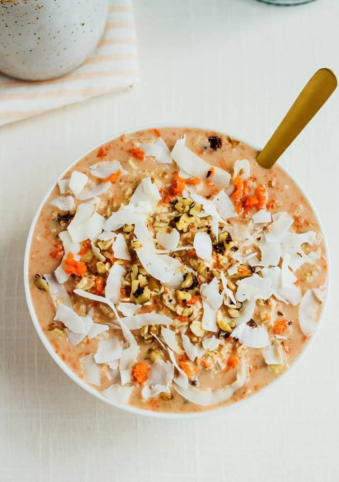 Bowl of carrot cake overnight oats topped with coconut and walnuts.