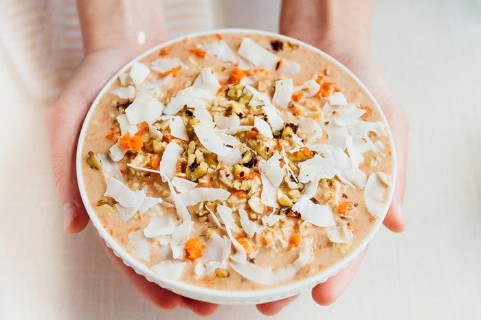 Hands holding a bowl of carrot cake overnight oats, topped with coconut and walnuts.
