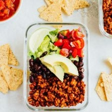 A glass dish with tempeh salad, including tempeh, black beans, lettuce tomatoes, and lime. Salsa, tempeh, and chips on the table on the side.