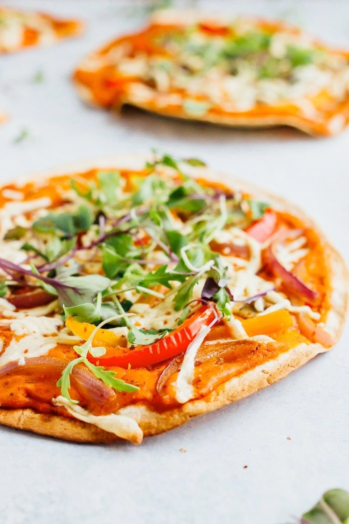 Tortilla pizzas topped with vegan cheese, peppers and greens and hummus.