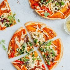 Sliced vegan hummus tortilla pizza with peppers, greens, and vegan cheese.