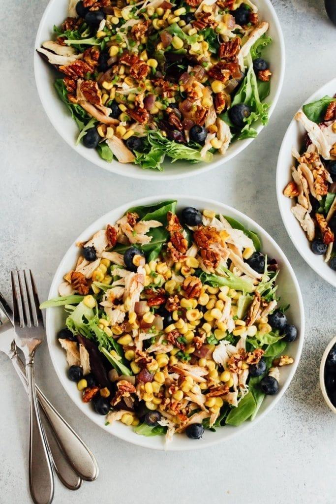 Three blueberry corn chicken salads with forks.