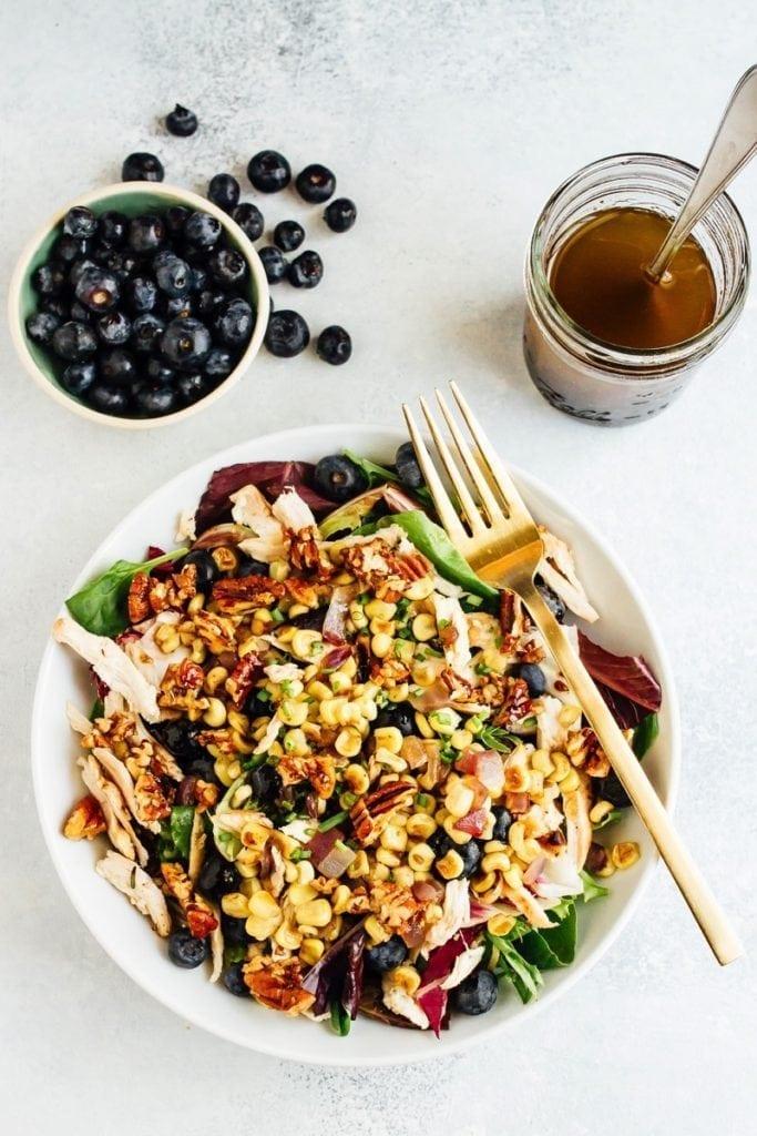 Salade de maïs aux bleuets avec une fourchette, bol de myrtilles et vinaigrette à part.