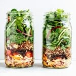 Layers of black bean fiesta mason jar salad, in two jars.