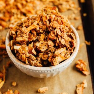 Bowl of granola on a baking sheet with parchment.