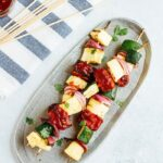 Grilled BBQ tempeh and veggie skewers on an oval platter, next to skewers on a towel.