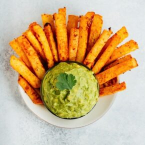 Golden Gut Baked Jicama Fries with Turmeric and Black Pepper and a dish of guacamole.