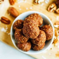 Pecan energy bites in a white bowl on a wooden cutting board.