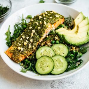Pesto salmon, greens, herbs, cucumber, and avocado over rice on a white plate.