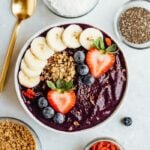 Maqui berry smoothie bowl topped with banana, strawberries, blueberries, and granola. Gold spoon laying beside the bowl along with bowls of dried berries, granola, coconut and chia.