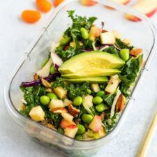 To go container with kale salad, edamame, apples, almonds, purple cabbage and slices of avocado.