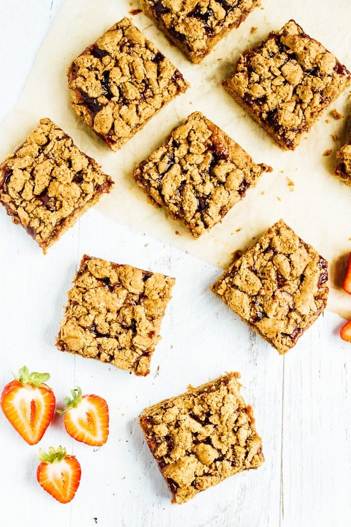 PB&J crumble bars lying on a table and parchment paper. Sliced strawberries are to the side.