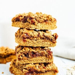 Stack of four pb&j bars. Bars filled with jam, topped with peanut butter crumble.