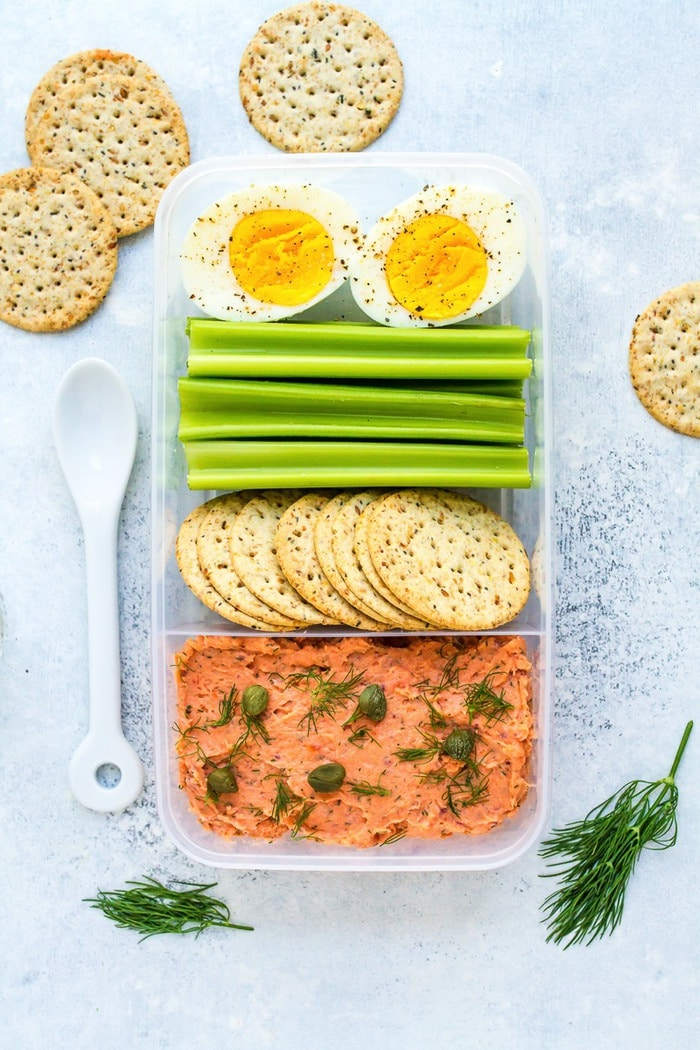 Packable lunch with smoked salmon dip, crackers, celery, and a hard boiled egg.