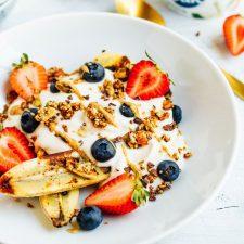 Yogurt bowl with banana, strawberries, granola, and nut butter.