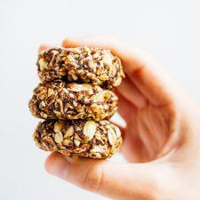 Hand holding three granola bites.
