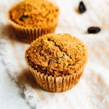 Two cinnamon raisin muffins in a peach and white striped towel with a few raisins sprinkled next to them.