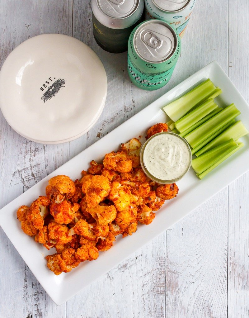 Looking for a healthy game day snack? Try these buffalo cauliflower wings with a creamy cashew dressing. They're absolutely delicious and easy to whip up. Vegan + gluten-free.