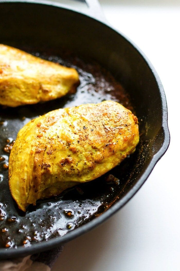 Maple turmeric chicken fully cooked in the cast iron skillet.