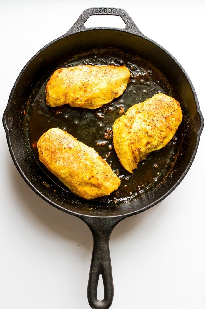 Overhead shot of maple turmeric chicken in cast-iron skillet, white background.