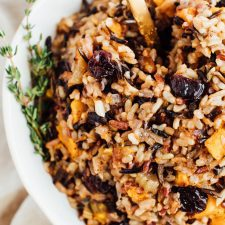 Bowl of wild rice stuffing with butternut squash and sweet cherries topped with thyme.
