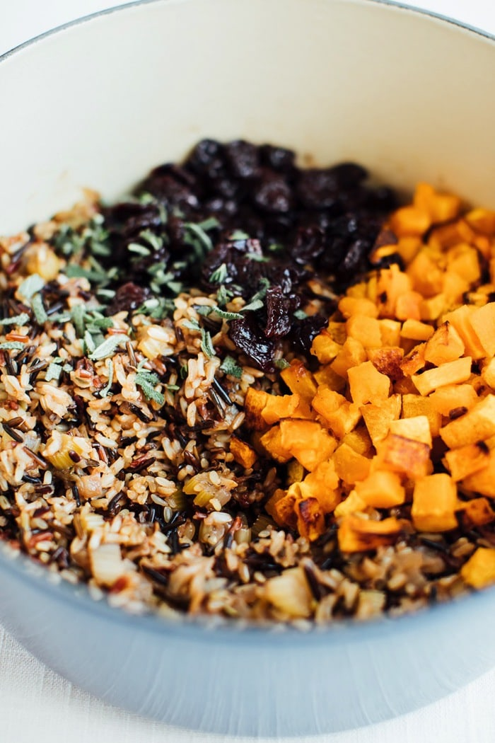 Ingredients for a wild rice stuffing in a bowl, including dried sweet cherries, roasted butternut squash, and thyme.