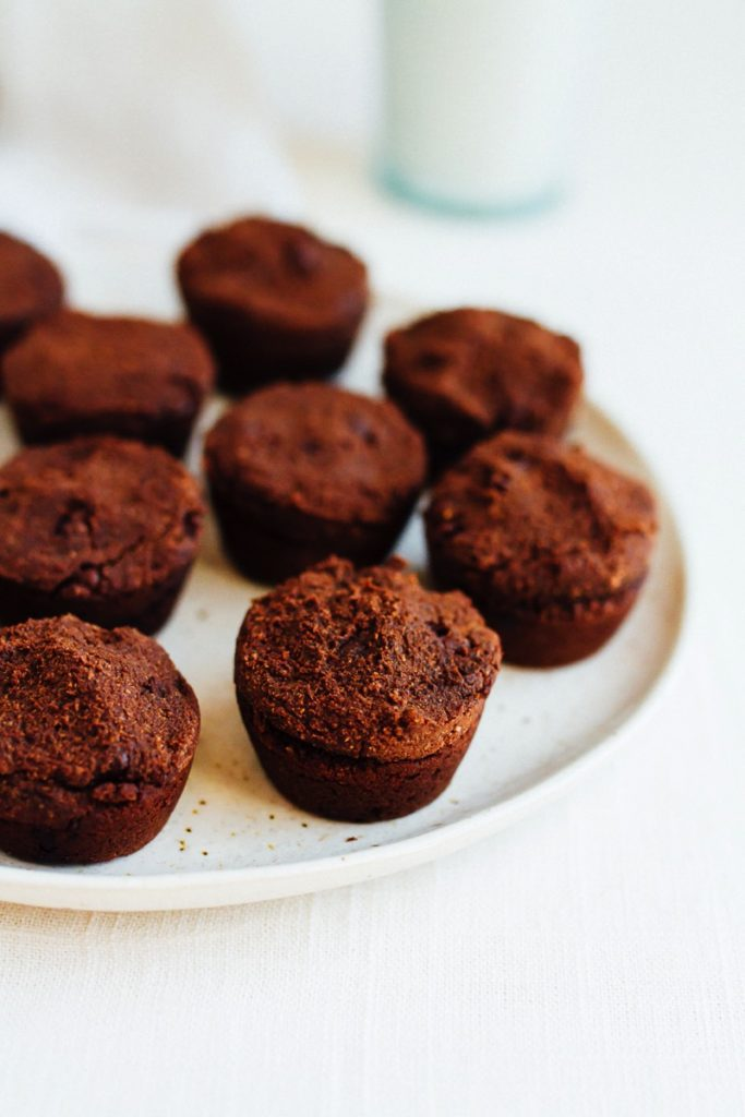 Gluten free and vegan sweet potato brownie bites stuffed with nut butter. Brownie bites are on a plate.