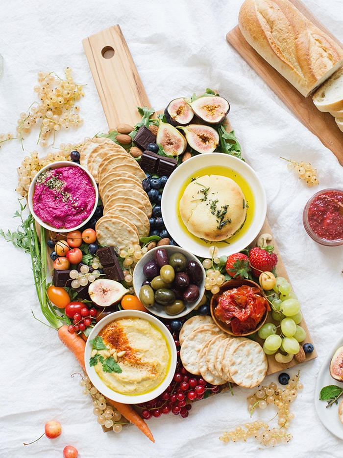 Assorted vegan fruits and veggies with crackers on a wooden cutting board.