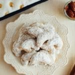 Almond flour crescent cookies on a snowflake plate next to a bowl of pecans and a gold polkadot pillow.