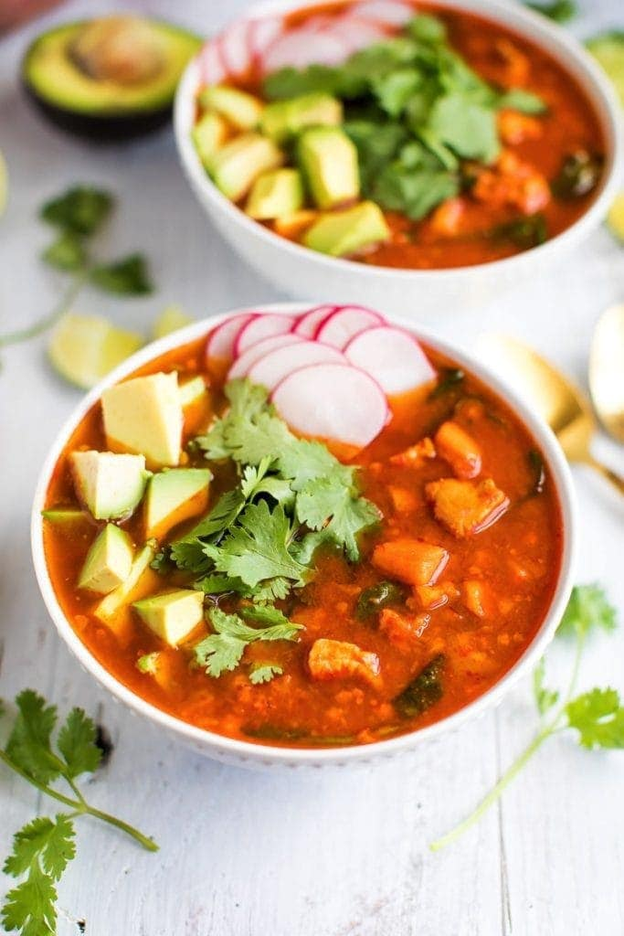 Mexican Sweet Potato chicken soup topped with cilantro, avocado and radishes.