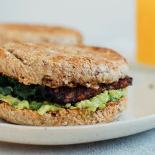 A vegan breakfast sandwich loaded with creamy avocado, almond butter, sautéed kale and tempeh bacon, on an english muffin.