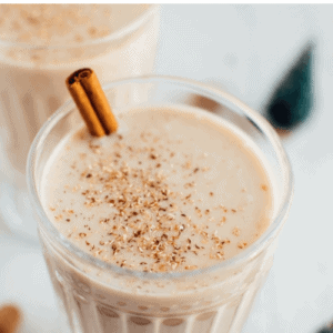 """Glass of clean eating eggnog garnished with a stick of cinnamon and grated nutmeg. Text above reads """"Clean Eating Dairy-Free Eggnog""""."""